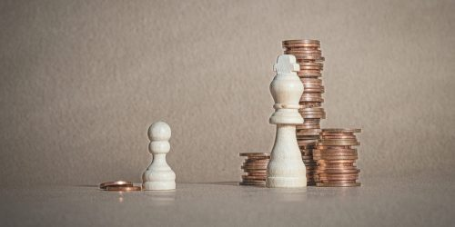 Chess pawn with a couple of coins in front of a king with lots of coins. Conceptual image.